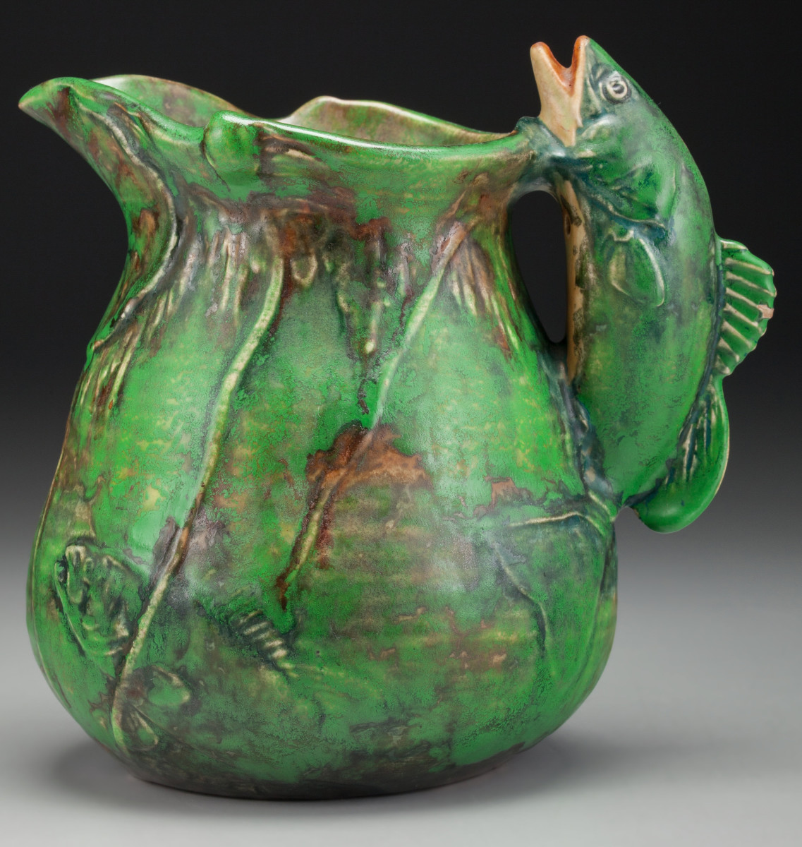 """Coppertone ceramic pitcher with molded and incised lily pad and fish decoration to the body and a molded fish-form handle, Zanesville, Ohio, circa 1925, 7-1/2"""" h; $525."""