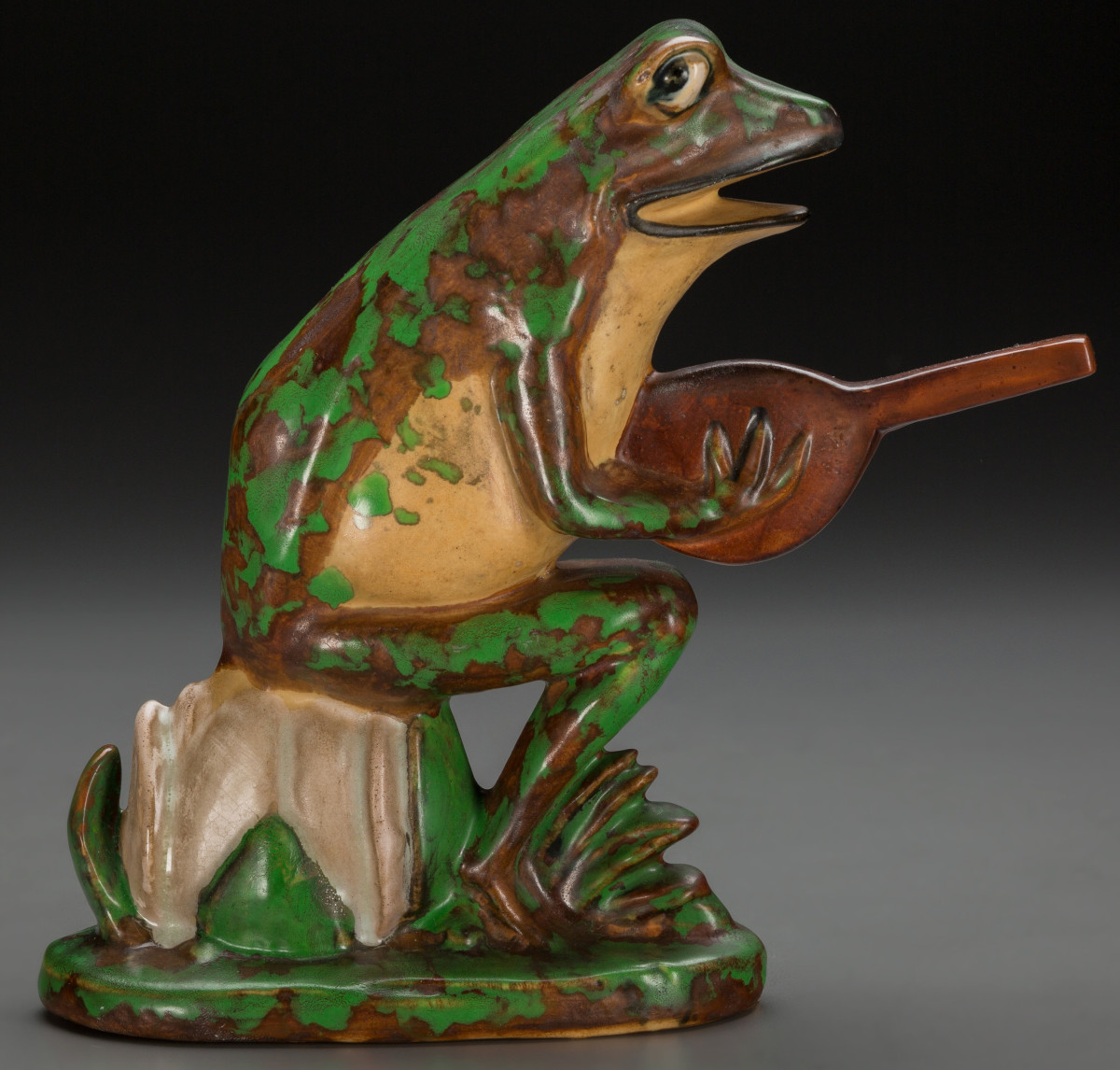 """This cheeky garden ornament features a frog playing a banjo - the instrument many people think they sound like. Zanesville, Ohio, circa 1925, """"Weller Pottery"""" mark (shown in the photo below), 7-1/4"""" h. This sold at auction in 2016 for $1,875."""