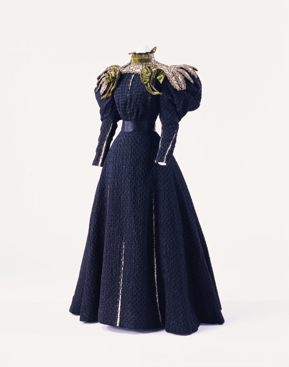 Day dress, c. 1895, Gustave Beer, Paris. Bouclé silk two-piece dress with gigot sleeves, collar and yoke of layered silk satin and twill with cut work and bead embroidery; crescent-shaped velvet decoration on collar and shoulders; beige silk satin visible through all-over slit.