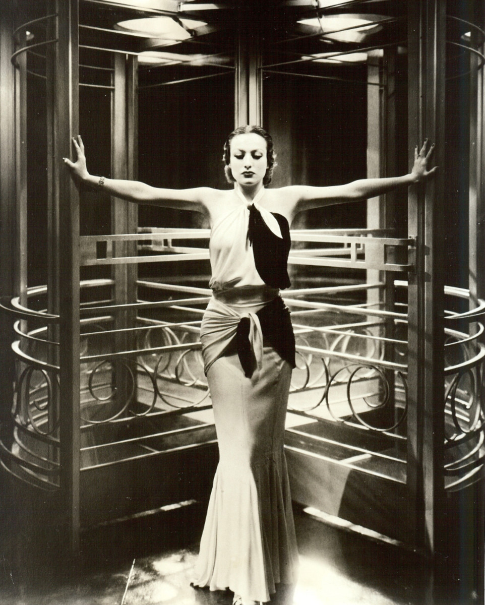 """In this publicity shot on the set of the movie, """"Grand Hotel,"""" Crawford wears another gown from Letty Lynton in the sleeker silhouette popular at the time. The gown is made of white crepe and black bugle beads."""