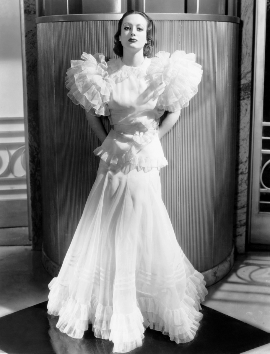 Joan Crawford wearing the famous Letty Lynton dress, 1932, designed by Adrian. It was knocked off by designers everywhere including Parisian couturiers.