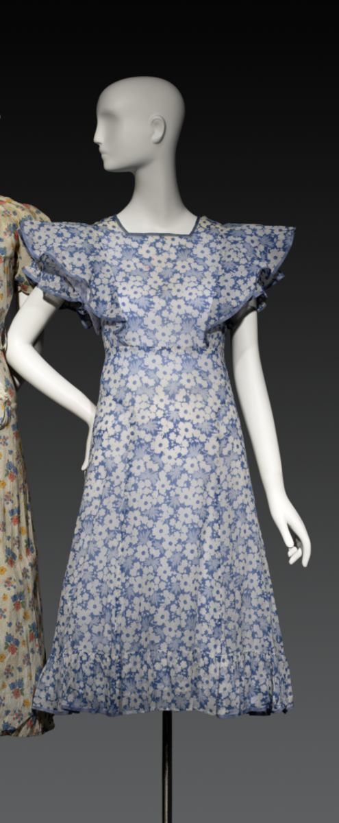 Blue and white floral-print house dress, c. 1933, maker unknown. During the Great Depression, many women refashioned old clothes into something new. This dress is a repurposed summer dress, and although the maker wore it to do housework and run errands, the large sleeves echo the Letty Lynton style. Even housewives at home wanted to look and feel like glamorous heroines.