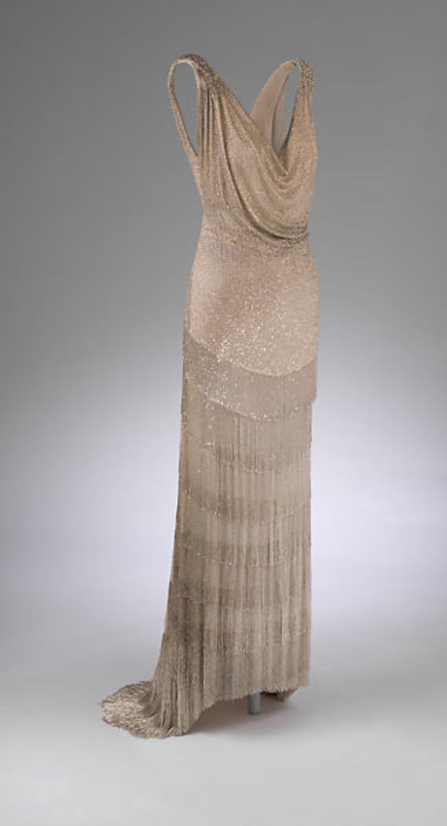 Dress by Jean-Charles Worth, 1931, demonstrating his talent for embracing a modern aesthetic and silhouette. Composed of silk tulle, the gown is densely embroidered with silver glass bugle beads that extend into deep layers of fringe and are worked into intricate braids at the shoulders.