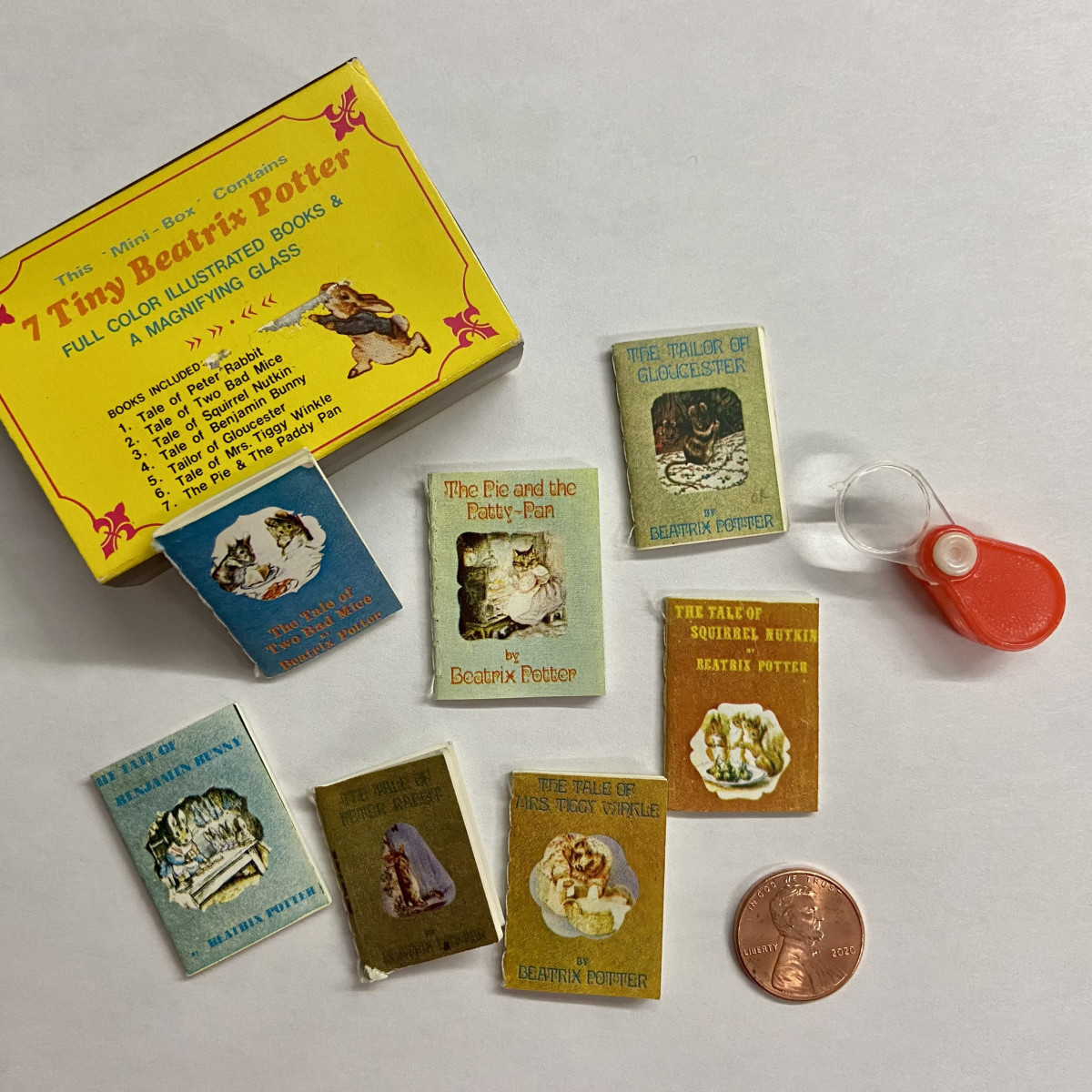 """A set of """"7 Tiny Beatrix Potter"""" books that are so tiny, it takes the included magnifying glass to read them; New York: Merrimack Publ. Corp., circa 1970 [unlicensed]."""