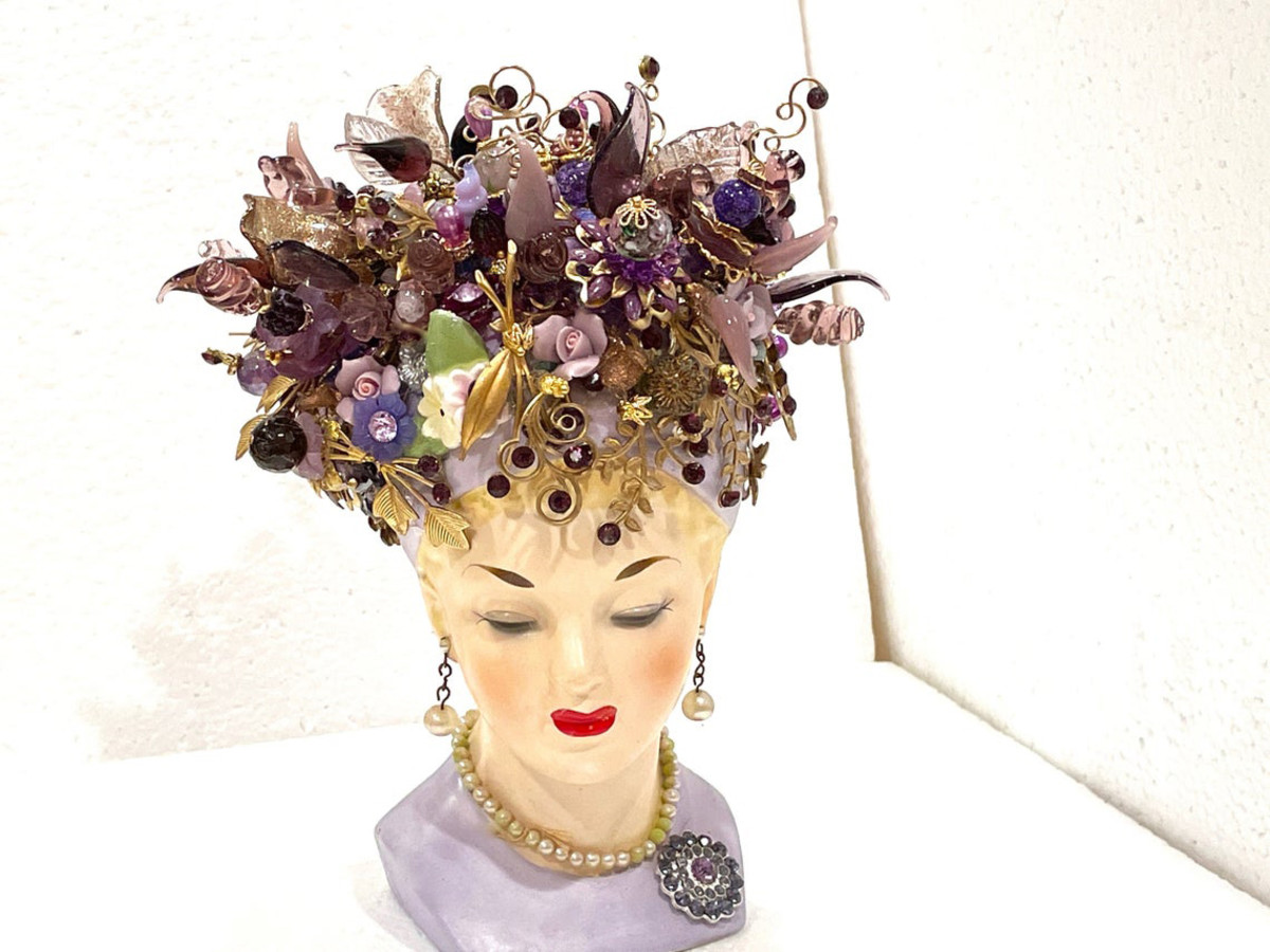 """Napco hand-painted amethyst lady head vase, 1960, signed and numbered, hand painted, original drop """"faux"""" pearl earrings and necklace,  and prong-set lavender rhinestone brooch on a lavender dress. Showcases over 80 handmade flowers, over 180 hand-set Swarovski crystals, 40 hand-torched flowers and leaves and over 30 hand-made brass fancy, swirled pins with rhinestones inset by the seller. Without flowers, 5-1/4"""" h, with flowers, 8-1/2"""" h; $320."""