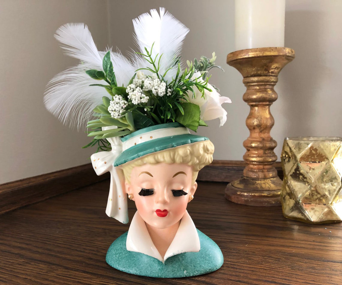 """Lucille Ball lady head vase, Napco, stamped C3959 ©NAPCO 1959, foil label is partially missing, bristle-fiber eyelashes, aqua green coat with white upturned, glazed collar and a wide-brimmed hat with polk-a-dot bow, 5-1/2"""". A crown of faux roses, greens, and feathers created by the seller is removable; $99.97."""