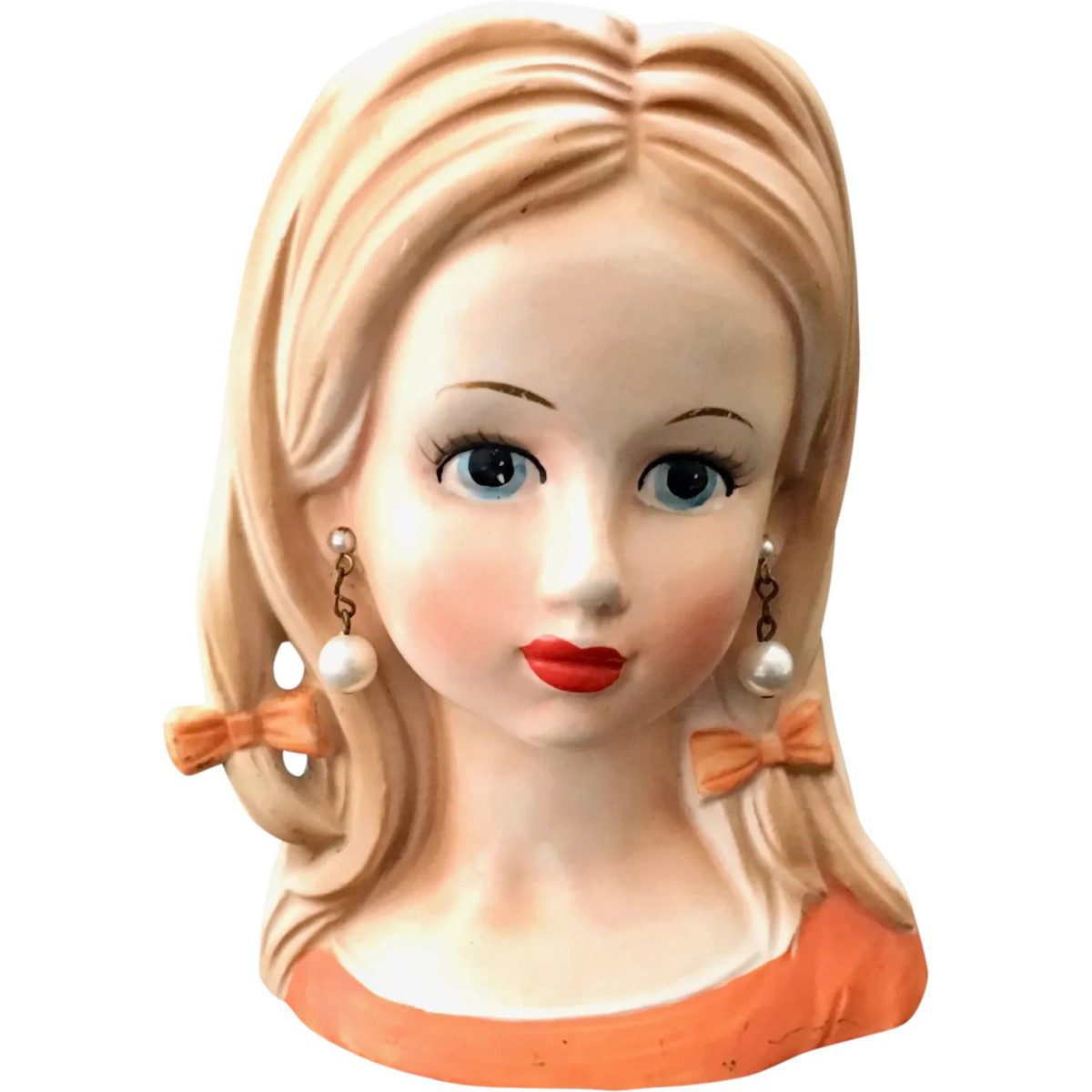 """A hard-to-find teen-age girl head vase by Relpo, with blonde hair, orange dress, pearl earrings and two hair bows, late 1950s-60s, stamped """"A639,"""" 5-1/2"""" h on a 3-3/4"""" x 2-3/4"""" base; $195."""