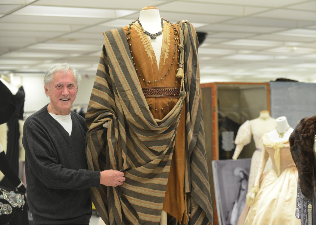 """Gene London in 2018 with a costume worn by Charlton Heston in """"Ben Hur"""" that was displayed, along with several other pieces, as part of Reading Public Library's """"Cocktails and Classics Fundraiser."""""""