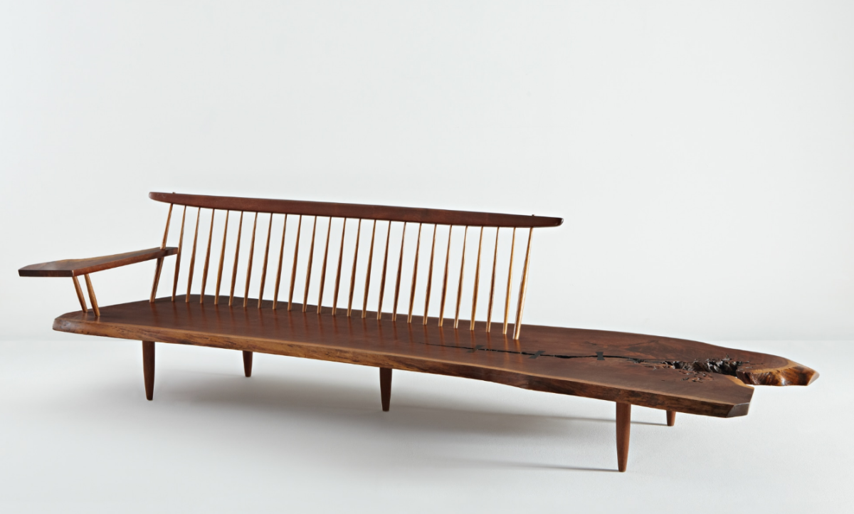 """George Nakashima early """"Conoid"""" bench with single free-form arm, 1961, American black walnut, hickory, three East Indian rosewood butterfly keys. 29-3/4"""" × 120"""" × 31-1/2""""; $230,500."""