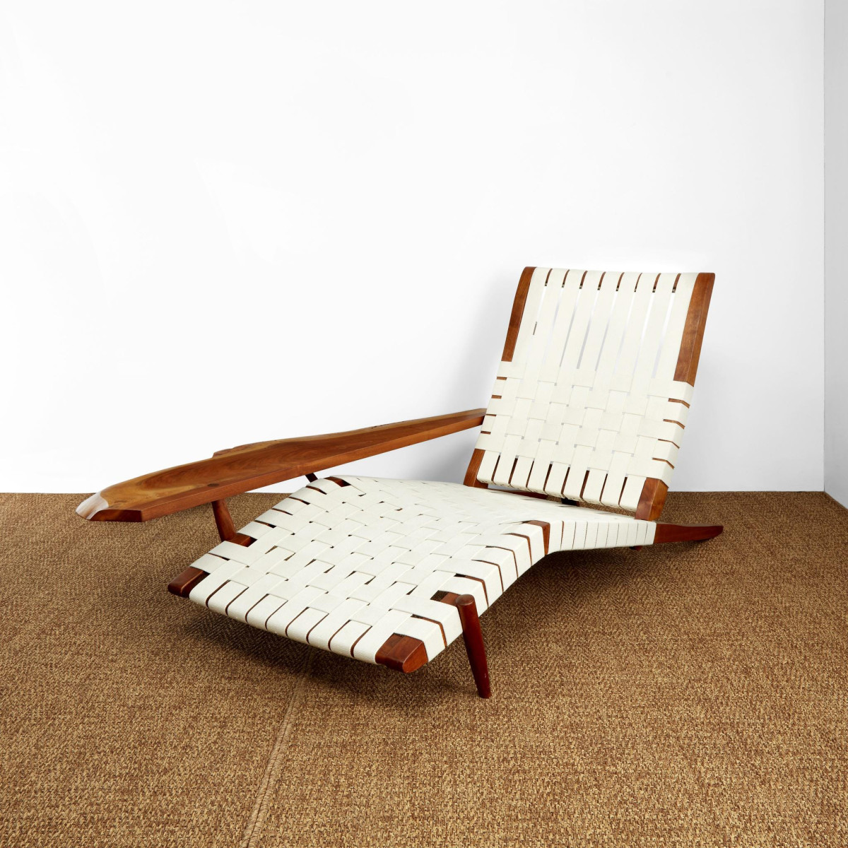"""George Nakashima """"Long"""" chair with arm, 1979, American black walnut, woven canvas, 31"""" h, 65-1/2"""" l, 38"""" w; $47,250."""