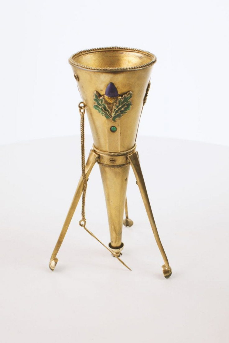 """Funnel-shaped tripod holder, circa 1880, silver with a gold wash, raised purple enamel flowers with green leaves on three sides, floral pin attached at the neck, legs collapse into a small spring-loaded retaining cup at the tip when carried in the hand, 4-1/2"""" h; $2,600."""
