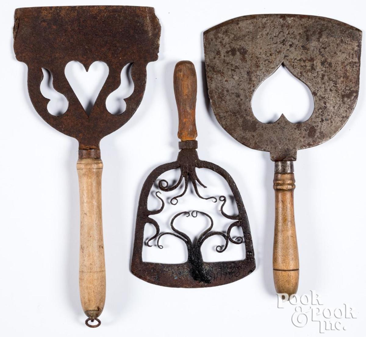 """Three wrought iron food choppers, 19th c., with pierced heart decoration, largest is 8"""" w; estimate: $160-$220."""