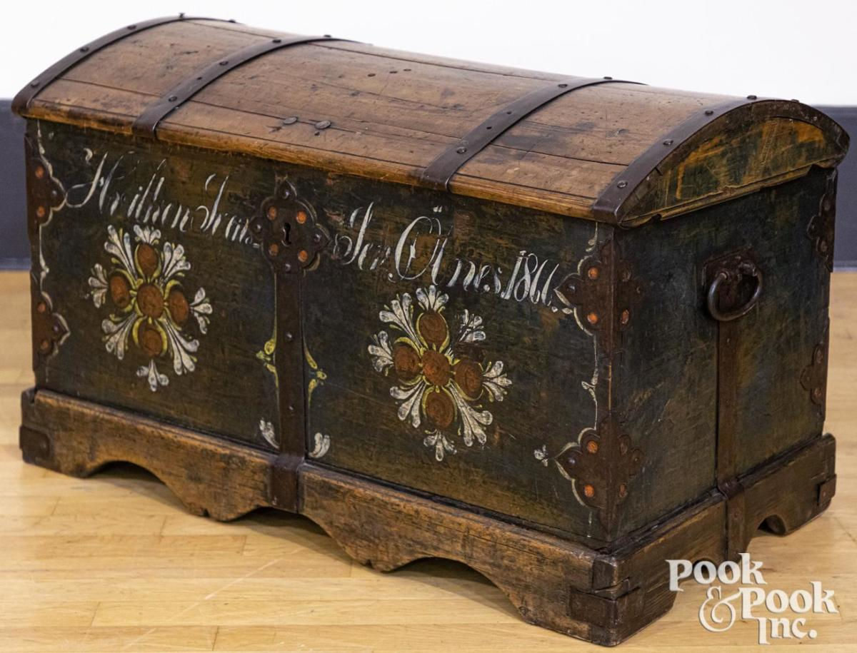 """Scandinavian painted pine immigrant trunk, dated 1866, retaining the original flower decoration on a blue ground with iron strapping, 22"""" h, 28"""" w; estimate: $200-$300."""