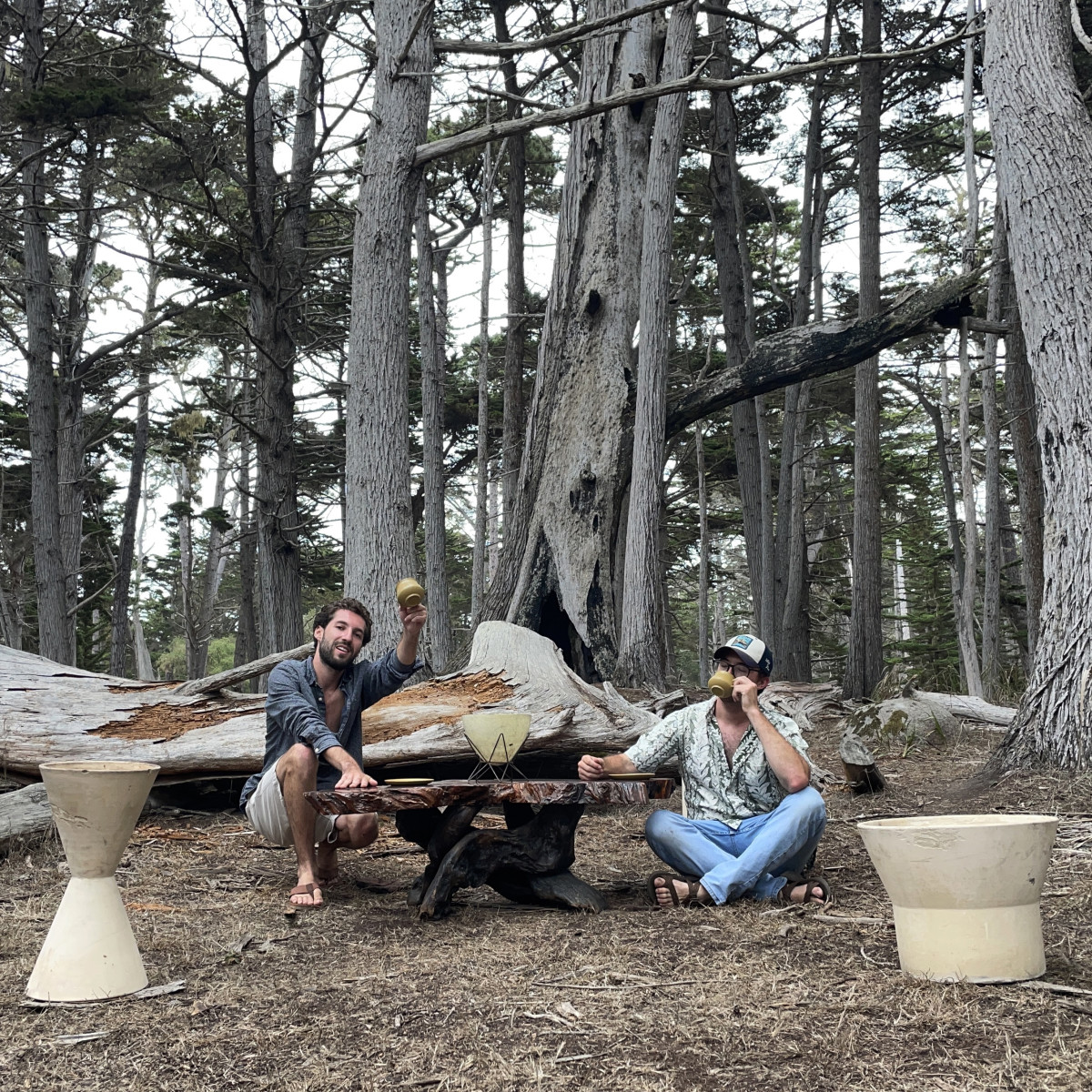 Chad and Bryce posing with a live-edge redwood coffee table and two Architectural Pottery planters  in a cypress forest outside of Monterey, California.