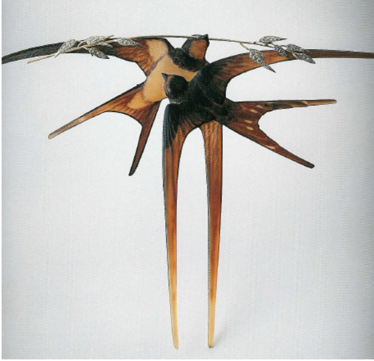 """Japanese hair combs captivated the European world when they were introduced at the Paris exhibition of 1867 and started a craze in France called Japonisme. The Japanese had a close relationship with nature, which produced some stunning jewelry, and Western artists, including Lalique, became influenced by this. The inspiration of nature, and the motif of swallows, which was common in Japan, is seen in this hair comb, """"Two Swallows with a Stalk of Oats."""" Circa 1906-1908, the comb is made of carved horn, gold and diamonds, and the bird's wings are elongated to form the its prongs."""